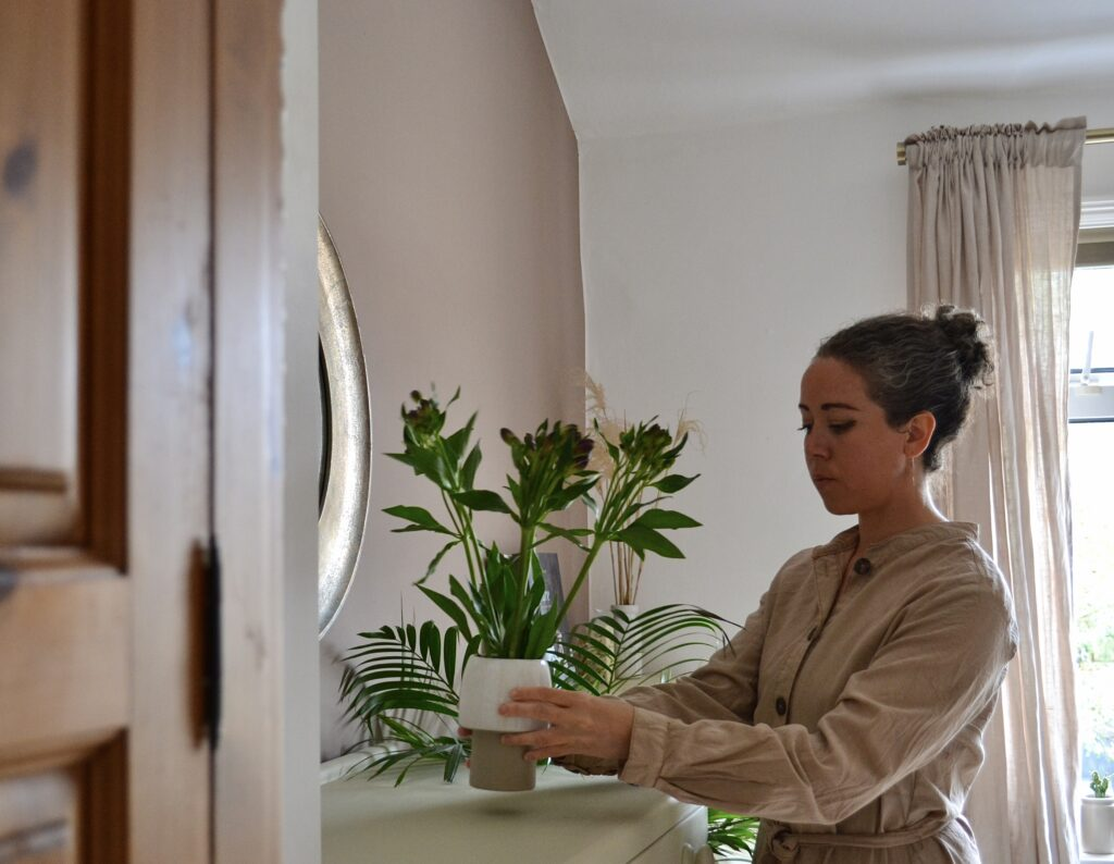 Zoe is arranging a plant on a counter top. She is wearing a natural, oat coloured shirt and her hair is pulled back in a neat bun.